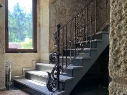 Barandilla de hierro forjado montada sobre escalera en curva en rehabilitación de vivienda.